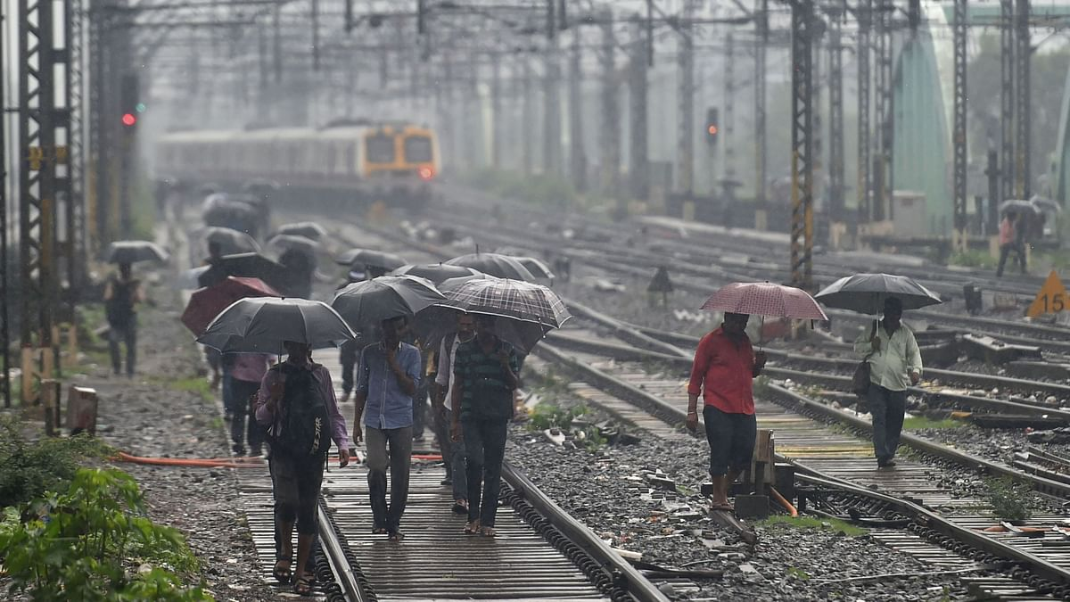 People walk on the railway tracks as heavy monsoon rains hit the central suburban trains service, in Mumbai, Tuesday, 2 July, 2019.