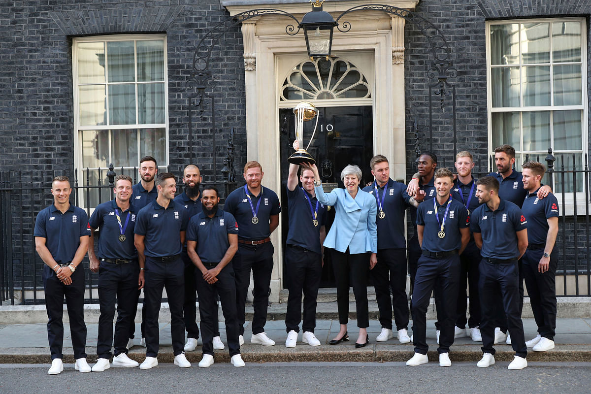 Britain's Prime Minister Theresa May smiles as she stands with England cricket captain Eoin Morgan, members of the team and the trophy after England won the Cricket World Cup, outside Downing Street in London.