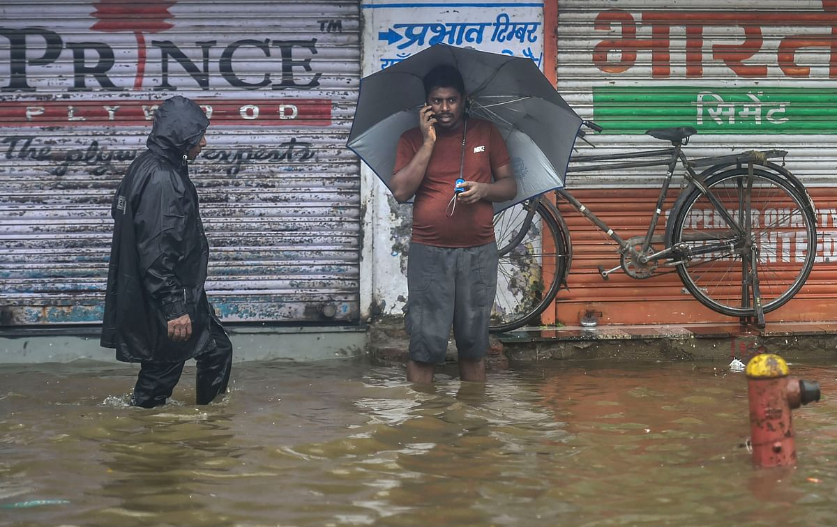 Pedestrians wade through a waterlogged street during monsoon rain.