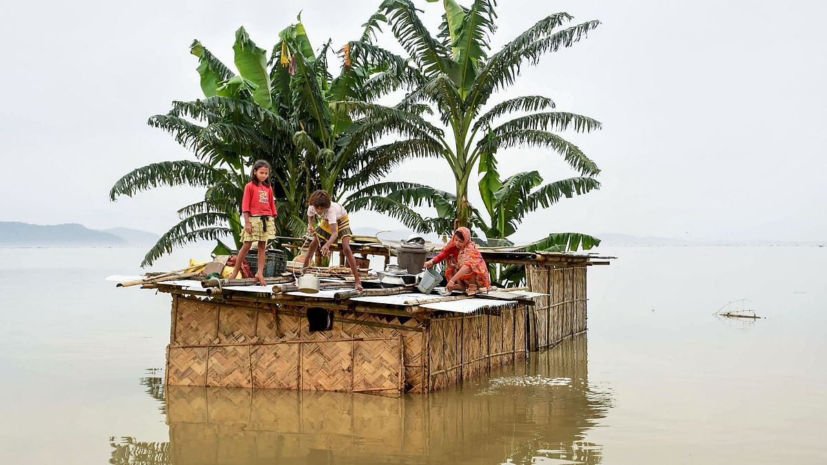A family marooned on the top of a hut in the flood-hit locality of Panikhaiti in Kamrup, Asssam on 15 July.