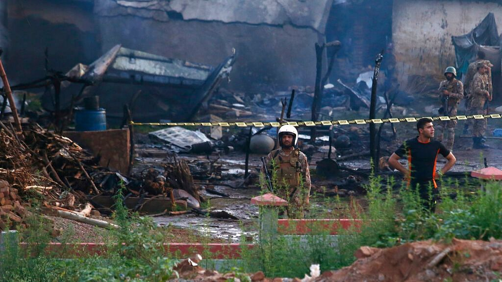 Pakistan army officials examine the site of a plane crash in Rawalpindi, Pakistan, on 30 July 2019.