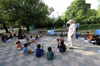 ISLAMABAD, Oct. 6, 2018 (Xinhua) -- A teacher attends a class at a makeshift school set up in a public park in Islamabad, capital of Pakistan, on Oct. 5, 2018. The World Teachers