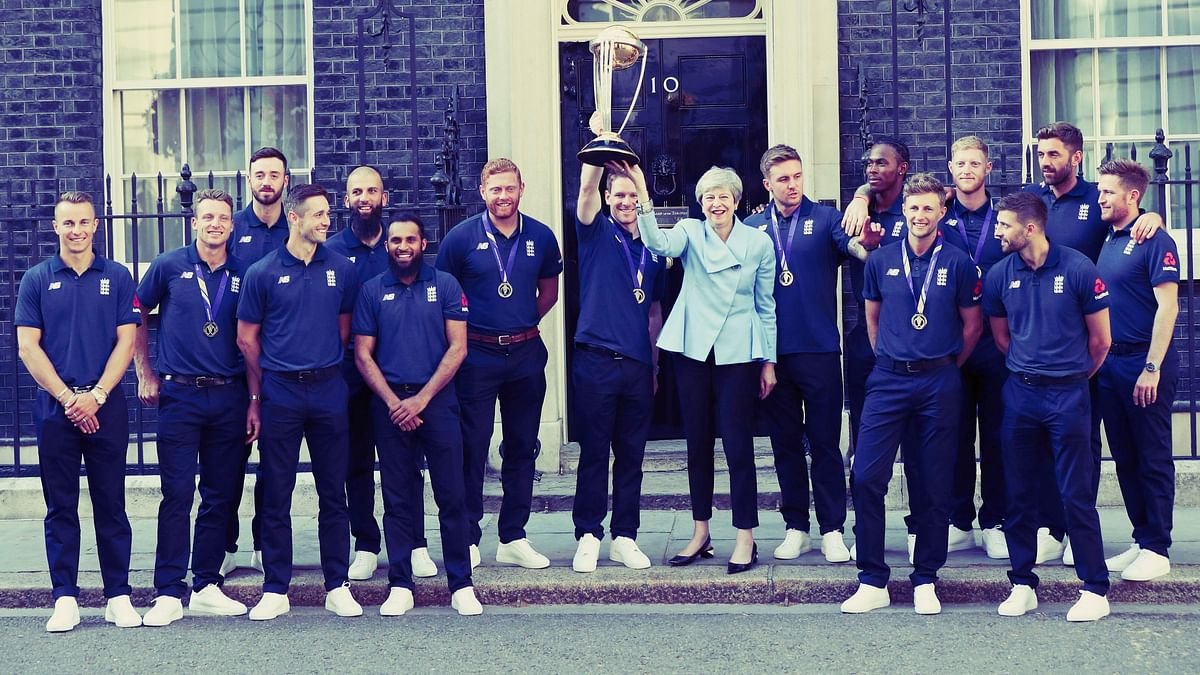 Britain's Prime Minister Theresa May smiles as she stands with England cricket captain Eoin Morgan and members of the team.