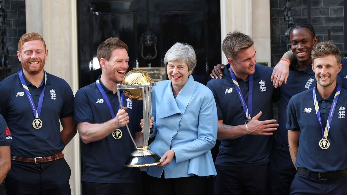 Britain's Prime Minister Theresa May smiles as she stands with England cricket captain Eoin Morgan, members of the team and the trophy after England won the Cricket World Cup, outside Downing Street in London, Monday, July 15, 2019. (Yui Mok/PA via AP)