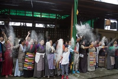 Dharamsala: Tibetans in exiles throw barley flour in air at the end of prayer session organised on the 81st birthday celebration of Tibetan Spiritual leader Dalai Lama in Dharamsala on July 6, 2016. (Photo: IANS)