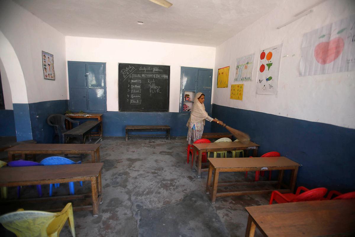 A Kashmiri school staff member cleans a deserted classroom in Srinagar.