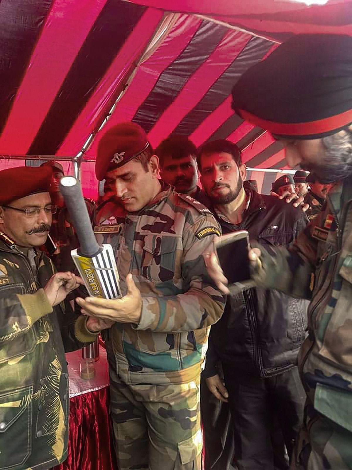 MS Dhoni in his Army uniform, signing a bat in Srinagar.