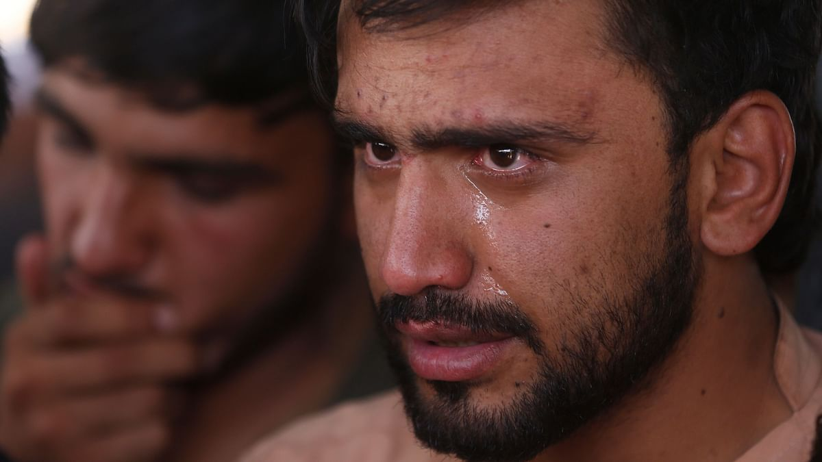 Relatives grieve near the coffins of victims of the Dubai City wedding hall bombing during a mass funeral in Kabul.