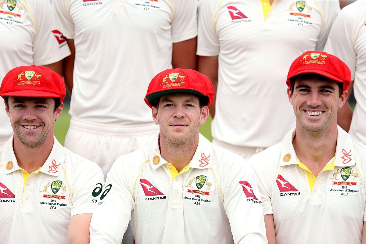 Australia's Tim Paine centre, Travis Head, left and Pat Cummins pose for a team photograph.