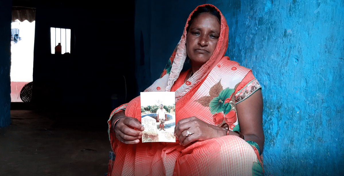 Vimla Devi holding the photo of her husband standing next to the newly constructed well.