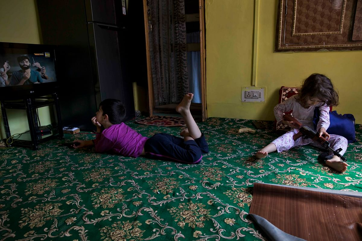 A Kashmiri boy watches television as his sister plays with a toy gun at home, in Srinagar.