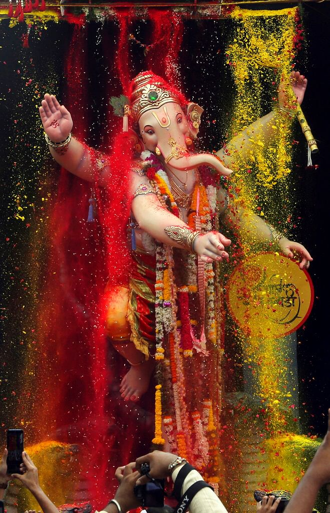 People take photographs of a giant idol of elephant-headed Hindu god Ganesha as it is taken for immersion on the tenth day of the ten-day long Ganesh Chaturthi festival in Mumbai. The festival is a celebration of the birth of Ganesha, the Hindu god of wisdom, prosperity and good fortune.