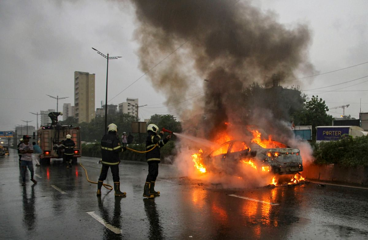 Fire personnel douse the flames on a car that caught fire on Chembur Road in Mumbai, Thursday, 26 September.