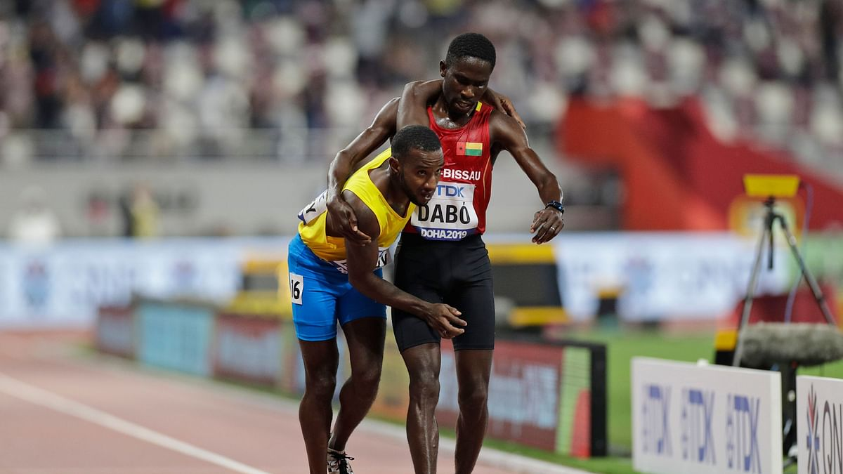 Braima Suncar Dabo of Guinea Bissau carries Jonathan Busby of Aruba to the finish line during the men's 5,000 meters heats during the World Athletics Championships Friday, Sept. 27, 2019, in Doha, Qatar.