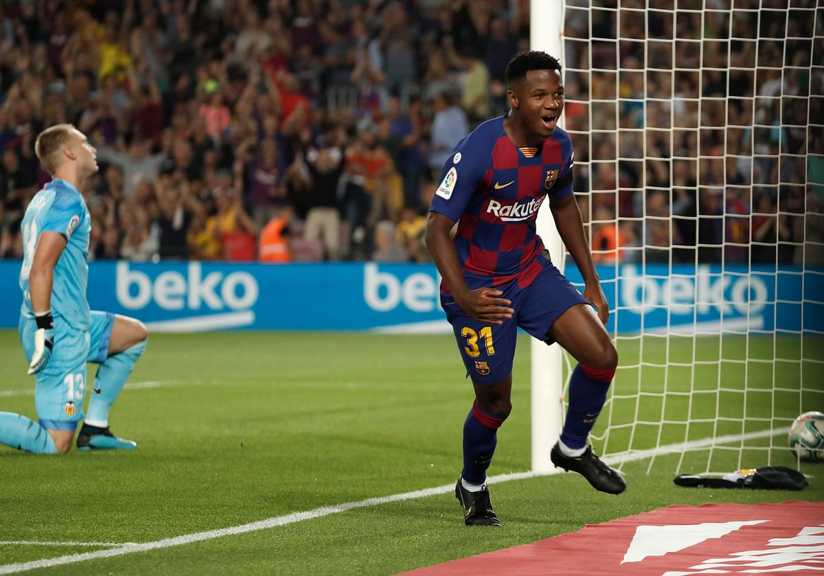 Barcelona's Ansu Fati, right, celebrates after scoring the opening goal as Valencia's goalkeeper Jasper Cillessen reacts during the Spanish La Liga soccer match between FC Barcelona and Valencia CF at the Camp Nou stadium in Barcelona.