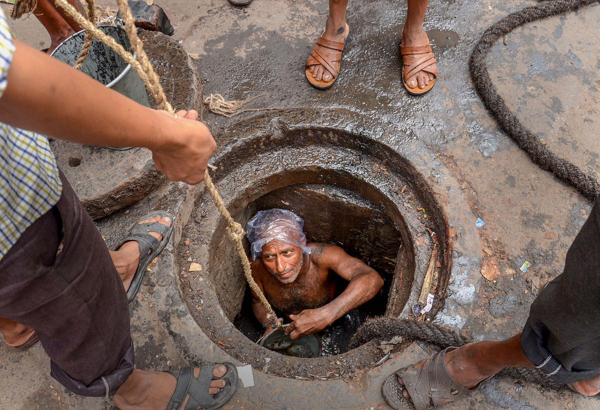 A Municipal Corporation worker enters a manhole for sewage cleaning at Mahatma Gandhi Road, in Kolkata.