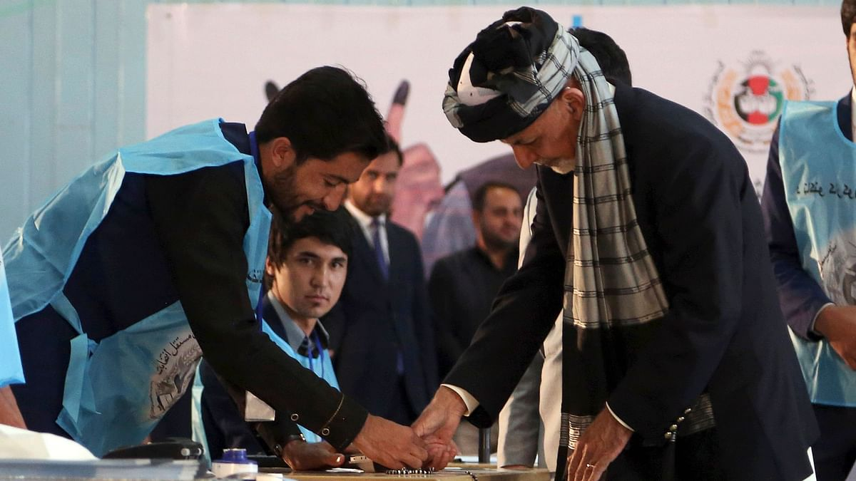 Afghan President Ashraf Ghani, right, inks his finger during the presidential election before he casts his vote at Amani high school, near the presidential palace in Kabul, Afghanistan, Saturday, 28 September, 2019.