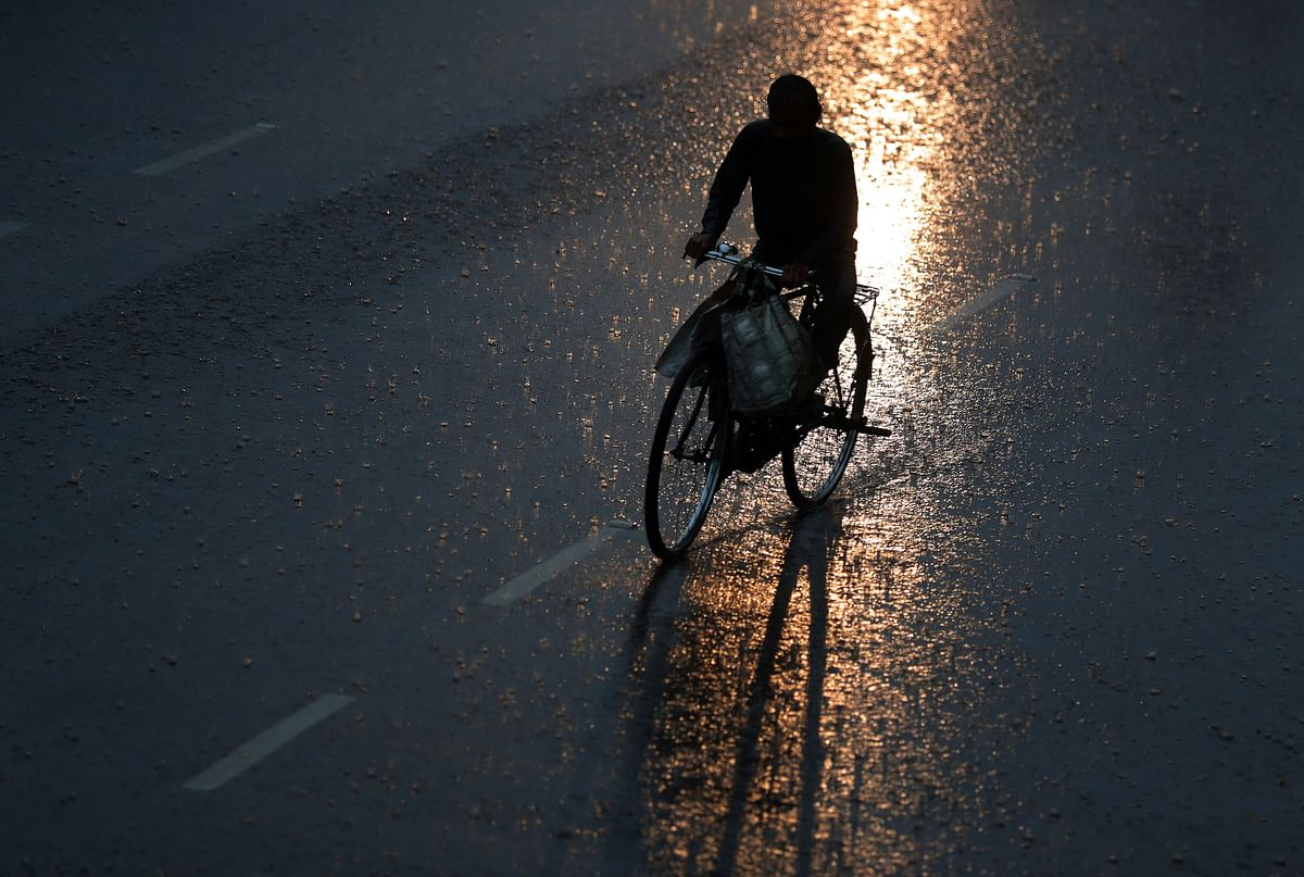 An Indian man rides a bicycle in the rain in Hyderabad, Tuesday, 24 September.