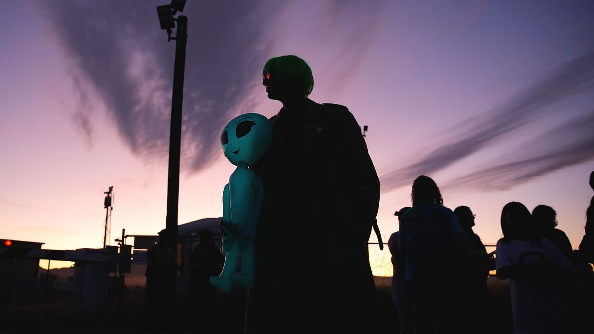Chase Hansen holds an inflatable alien near an entrance to the Nevada Test and Training Range near Area 51, Friday