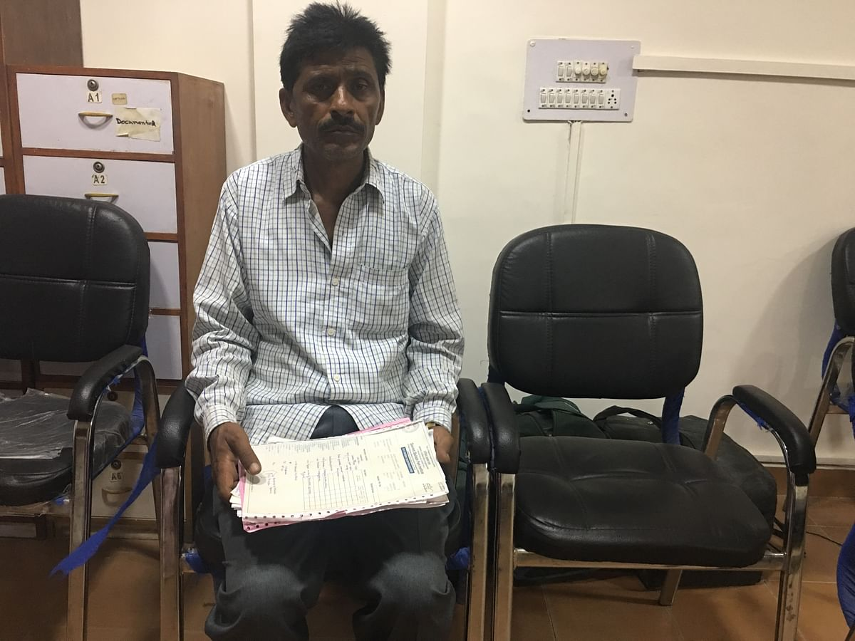Ruman's father, Hashimuddin Safi, sitting with his daughter's medical file.