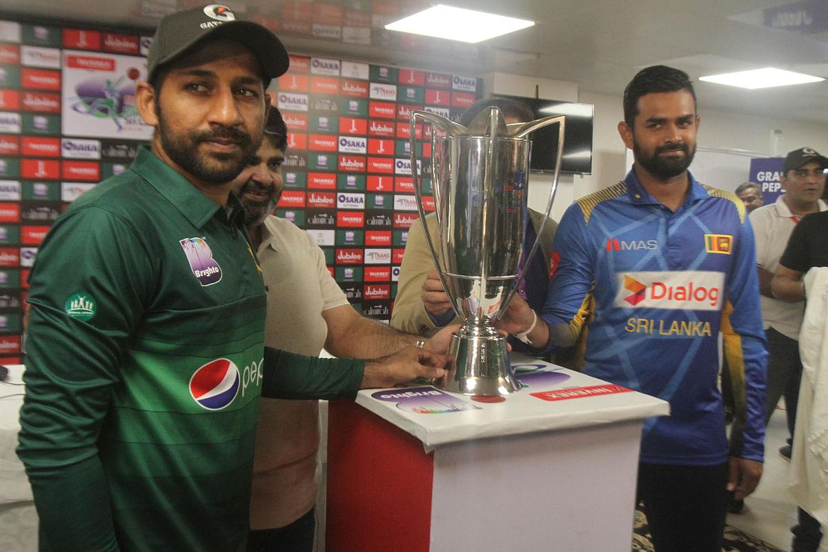 Sri Lanka captain Lahiru Thirimanne, right, and his Pakistani rival Sarfaraz Ahmed stand with a trophy, in Karachi, Pakistan, Thursday, Sept. 26, 2019.