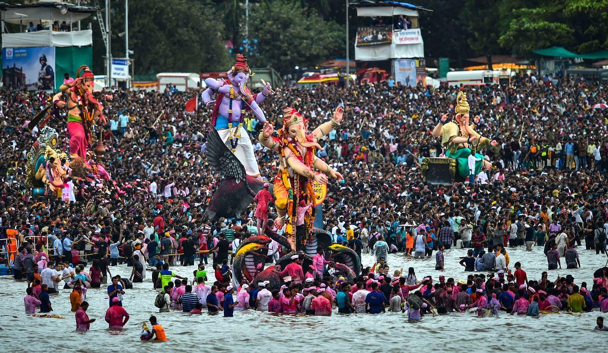 Devotees carry Ganesha idols for immersion to mark the end of Ganesh Utsav celebrations, at Girgaum Chowpatty in Mumbai on 12 September.