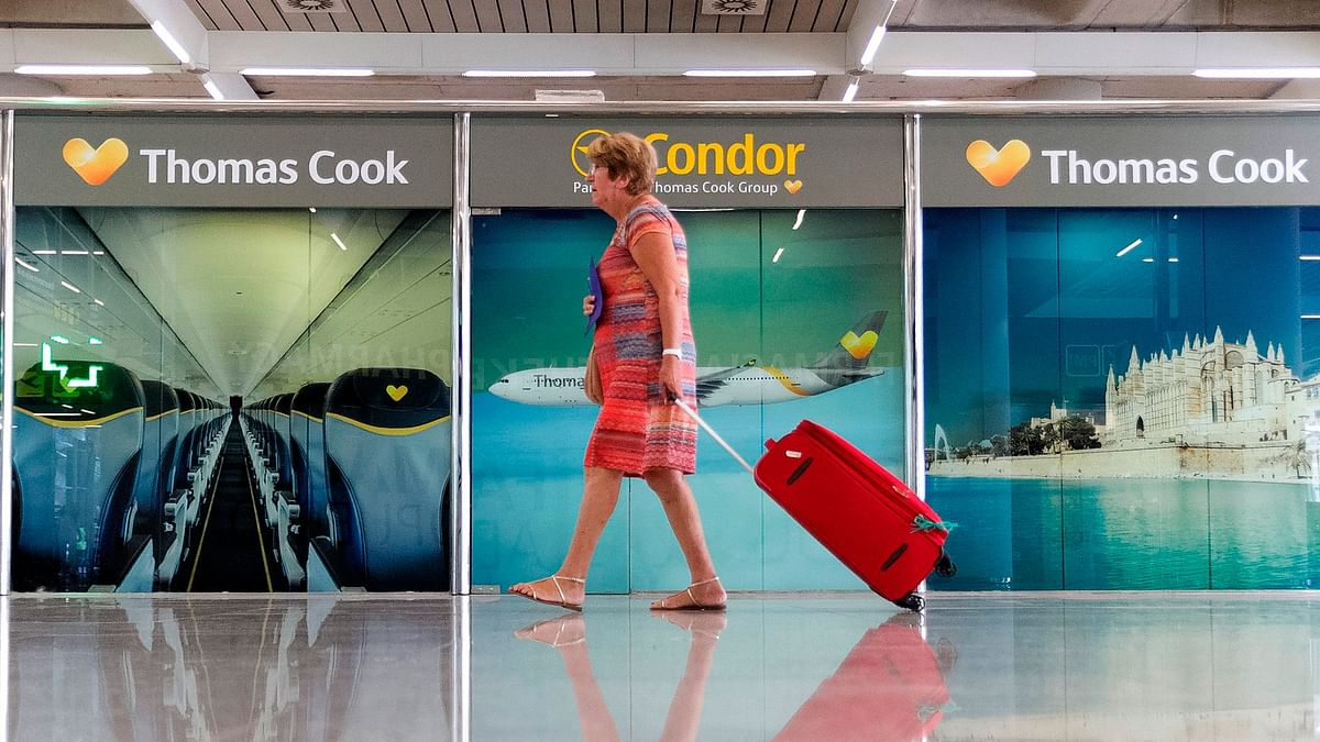 A passenger walks past a closed Thomas Cook office at Palma de Mallorca airport on Monday.