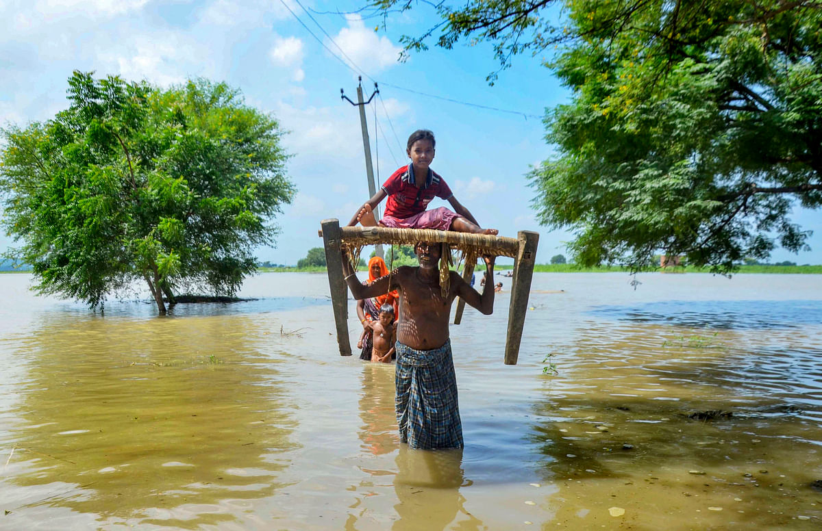 Villagers relocate to a safer place after their houses get flooded due to River Ganga rising following monsoon rainfall, at Narsinghpur village in Mirzapur.