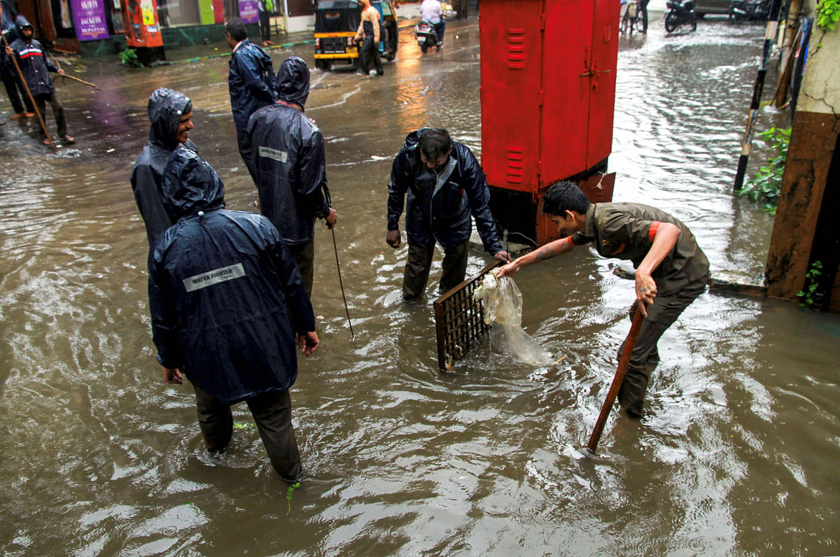 <b> Municipality workers unclog a drain following heavy monsoon rains in Thane on 4 September.</b>