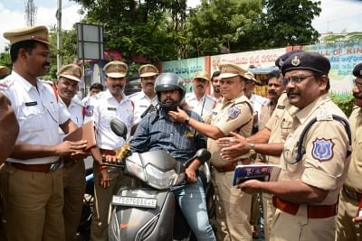 Hyderabad: Policemen give a helmet to a motorcyclist instead of challans in Hyderabad. (Photo: IANS)