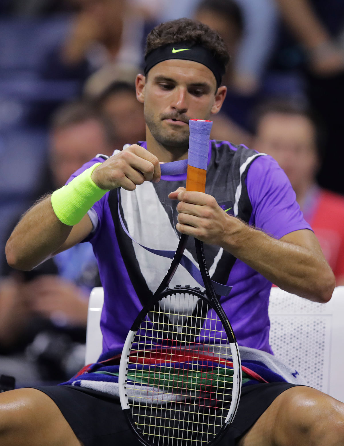 Grigor Dimitrov, of Bulgaria, tapes his racket grip before facing Roger Federer, of Switzerland, in the fifth set during the quarterfinals of the U.S. Open tennis tournament Tuesday, Sept. 3, 2019, in New York.