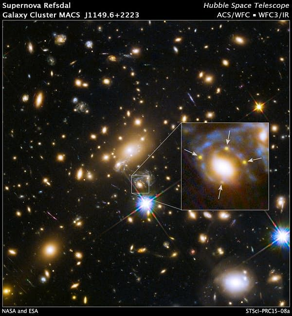 A large cluster galaxy (centre of the box) has split the light from an exploding background supernova into four yellow images/dots.