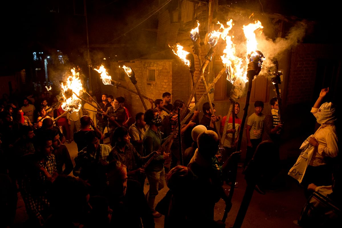 Kashmiri men shout slogans during a torch light march urging world leaders to protest  the decision to strip Jammu and Kashmir of semi-autonomy and statehood, in Srinagar, Thursday, 26 September.