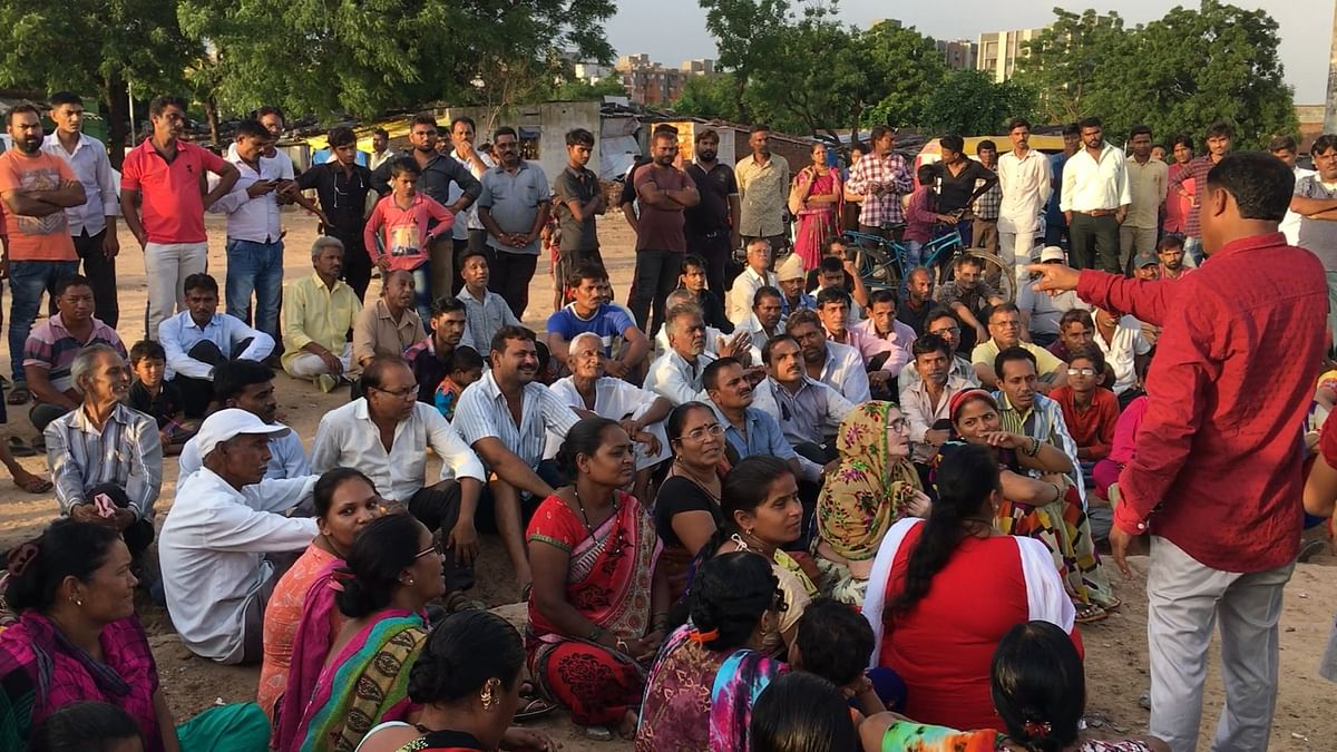 Members of RDAM speak with the now homeless residents of the low income housing scheme in Odhav, Ahmedabad.