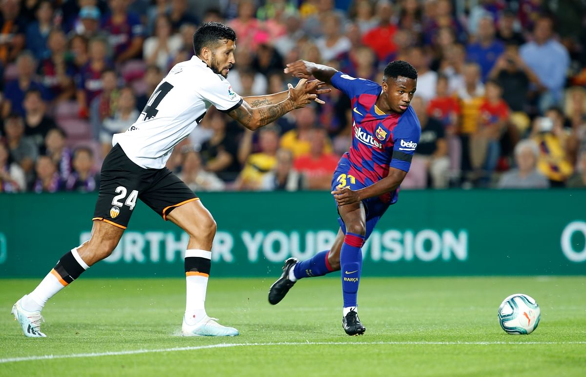 Valencia's Ezequiel Garay, left, fights for the ball with Barcelona's Ansu Fati, right, during the Spanish La Liga soccer match between FC Barcelona and Valencia CF at the Camp Nou stadium in Barcelona, Spain, Saturday, Sep. 14, 2019.