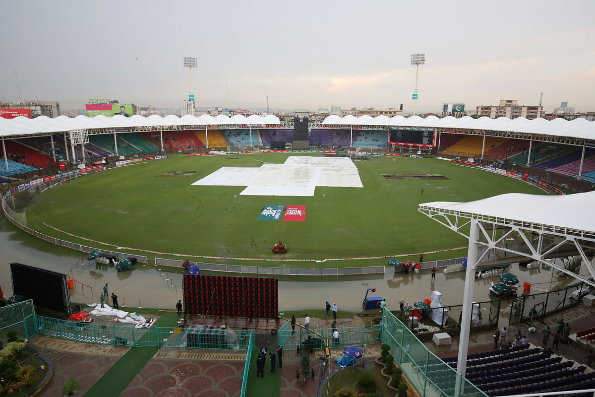Officials cover the ground of the National Stadium after a rain in Karachi, Pakistan, Friday, Sept. 27, 219. Heavy rain has delayed the start of the first one-day international between Pakistan and Sri Lanka.