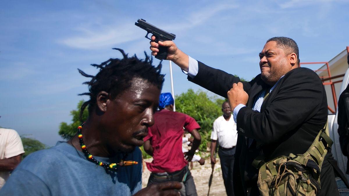 Ruling party Senator Ralph Fethiere fires his gun outside Parliament in Haiti
