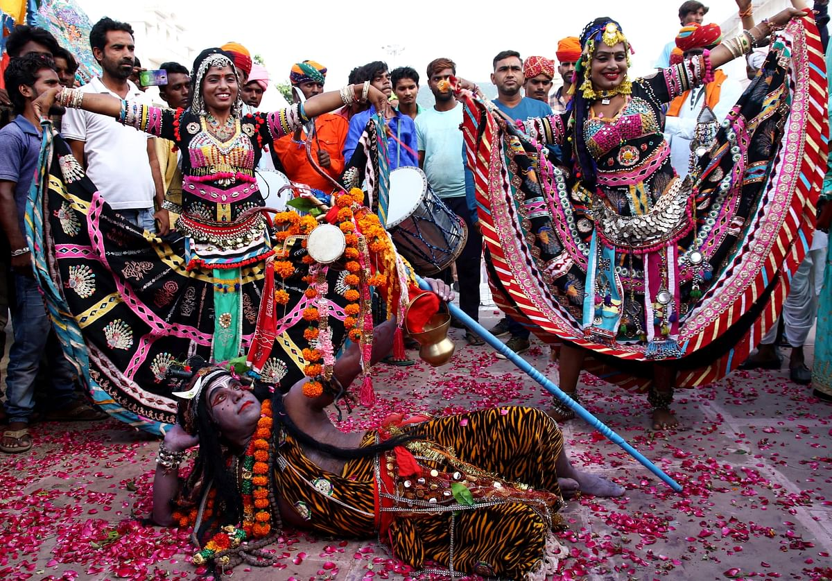 A man dressed as Lord Shiva poses as Rajasthani folk artists dance on the eve of World Tourism Day in Pushkar, Rajasthan, Thursday, 26 September.