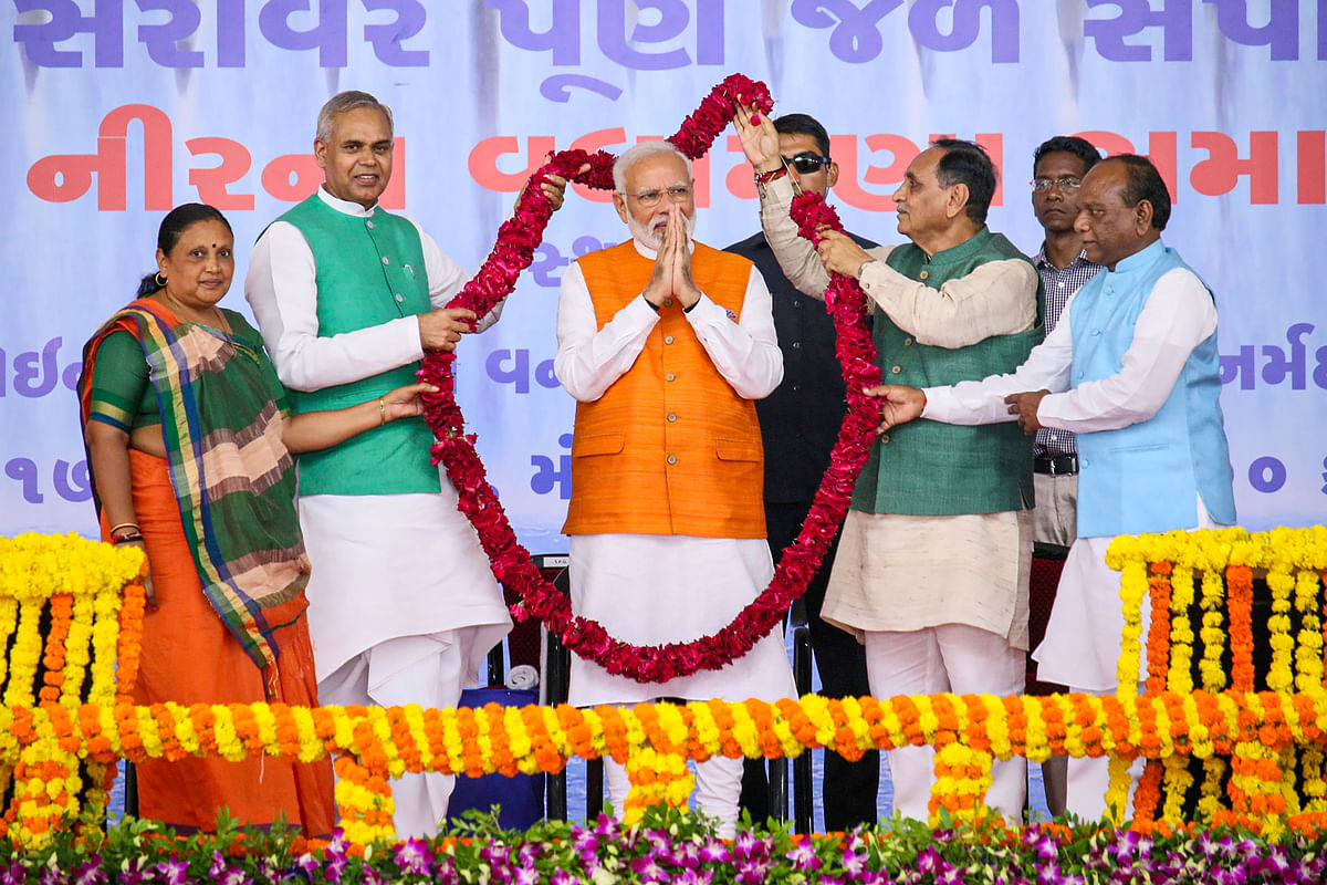 PM Modi being garlanded Gujarat Governor Acharya Devvrat and Chief Minister Vijay Rupani during a welcome ceremony in Narmada.