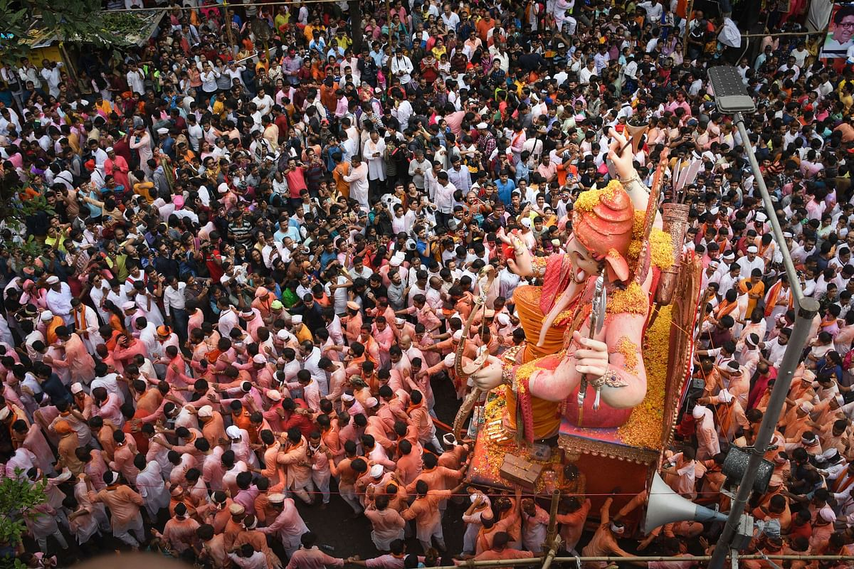 People watch as devotees carry an idol of Lord Ganesha for immersion, which marks the end of Ganesh Utsav celebrations, in Mumbai, on Thursday, 12 September 2019.