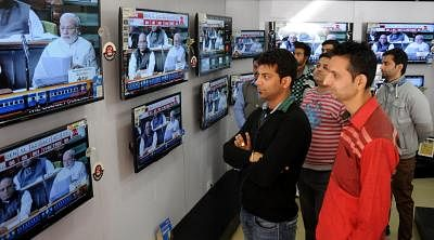 Amritsar: People glued to the television screens as Union Railways Minister Suresh Prabhakar Prabhu presents Railway Budget 2015-16 at the Parliament, in Amritsar, on Feb 26, 2015. (Photo: IANS)