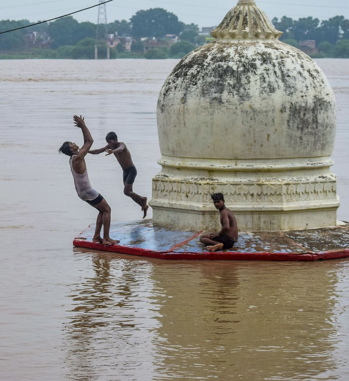 Youths jump into the floodwater at a flood-hit area following the rise in Ganga River due to monsoon rainfall, in Prayagraj.