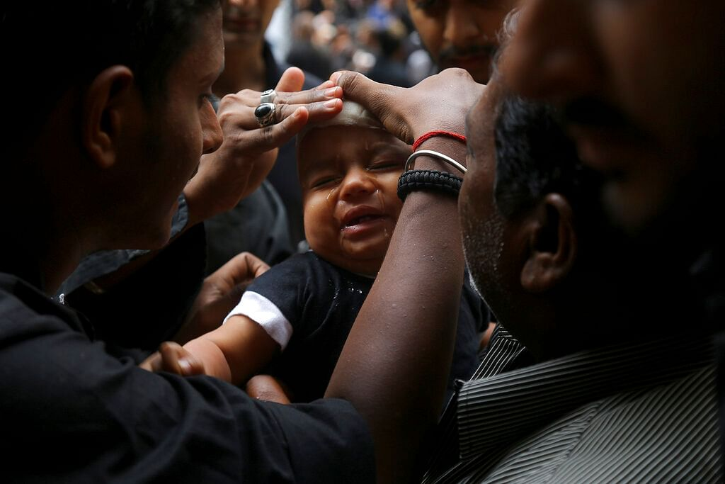 Shiite Muslim child cries after he was given a cut on the forehead during an Ashoura procession in Hyderabad, Telangana.