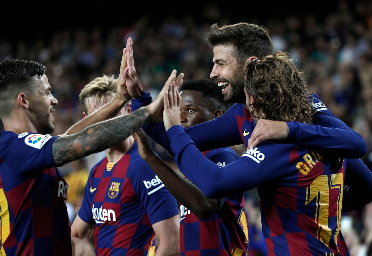 Barcelona's Gerard Pique, second right, celebrates with teammates after scoring his side's third goal during the Spanish La Liga soccer match between FC Barcelona and Valencia CF at the Camp Nou stadium in Barcelona, Spain.