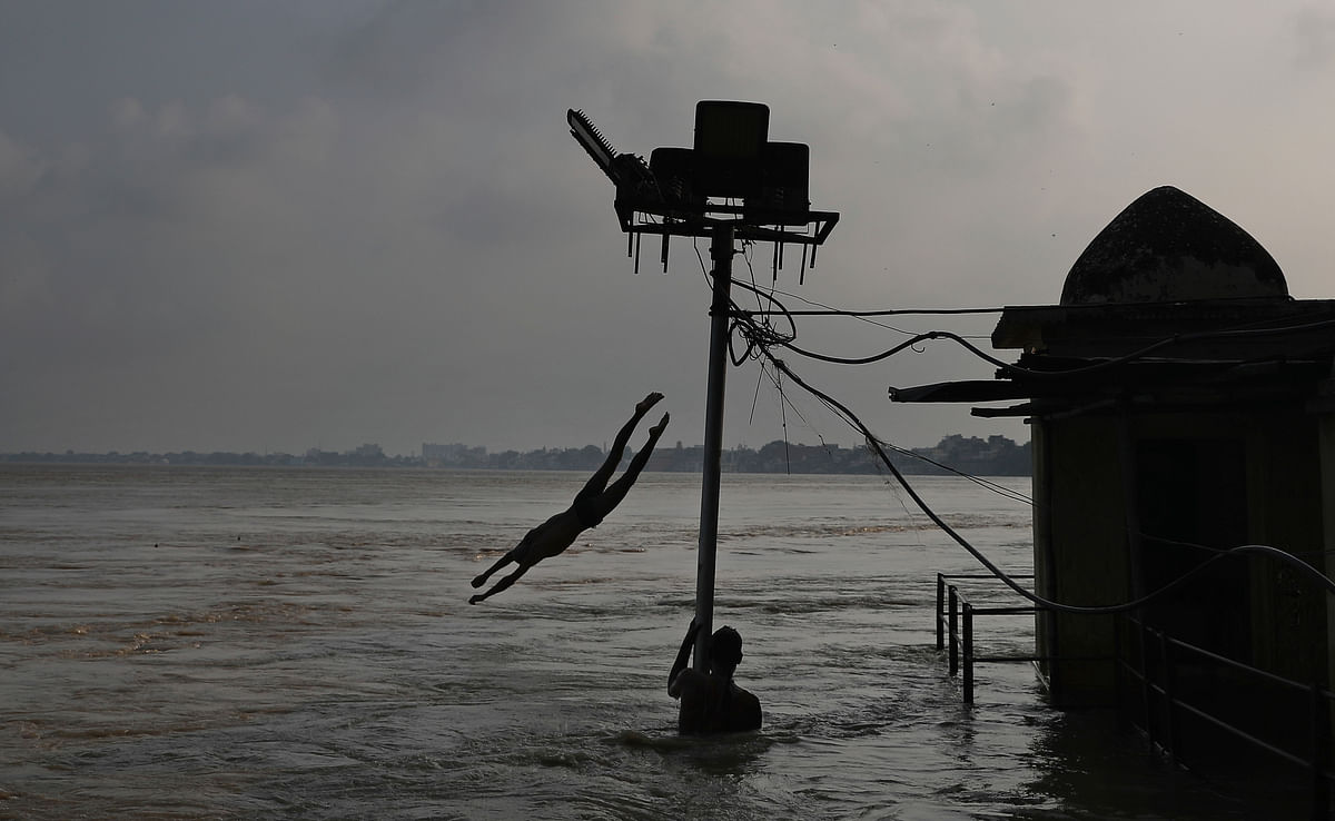 A boy jumps from the roof of a building into the waters of the swollen River Ganga as another boy holds onto a partially submerged electric pole in Varanasi, India, Sunday, 22 September.
