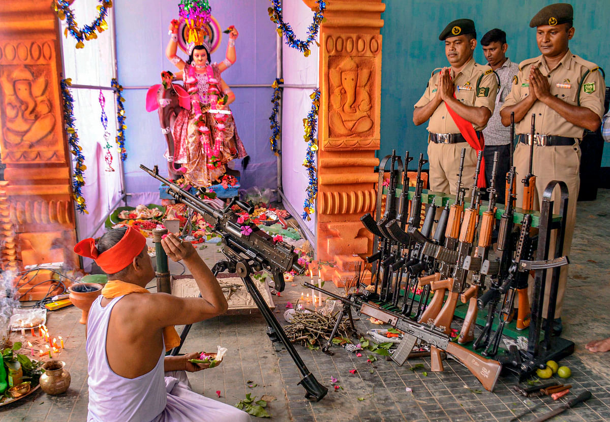 A priest performs worship of weapons on the occasion of Vishwakarma Puja at 2nd Tripura State Rifles Battalion at Bodhjungnagar,  Agartala.