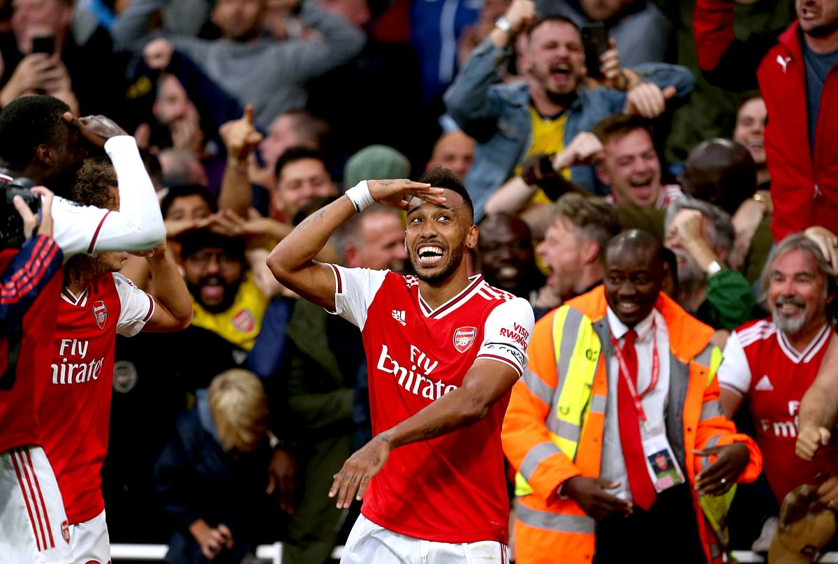 Arsenal's Pierre-Emerick Aubameyang (centre) celebrates scoring his side's third goal of the game during the Premier League match at the Emirates Stadium, London. PA Photo.