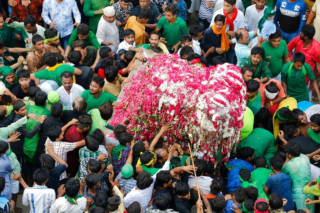 Indian Shiite Muslims take out a tableau in a religious procession to mark the Muslim festival, Prayagraj, India on Tuesday, 10 September. Ashoura, the tenth day of the lunar Islamic month of Muharram, is marked by Shiite believers as the day that Imam Hussein, the grandson of prophet Muhammad and one of their most revered saints, was killed in the battle of Karbala in the year 680 AD.