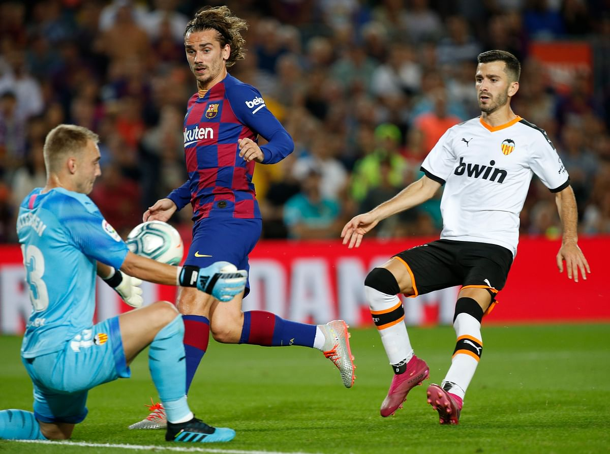 Valencia's goalkeeper Jasper Cillessen makes a save ahead of Barcelona's Antoine Griezmann, centre, during the Spanish La Liga soccer match between FC Barcelona and Valencia CF at the Camp Nou stadium in Barcelona, Spain.