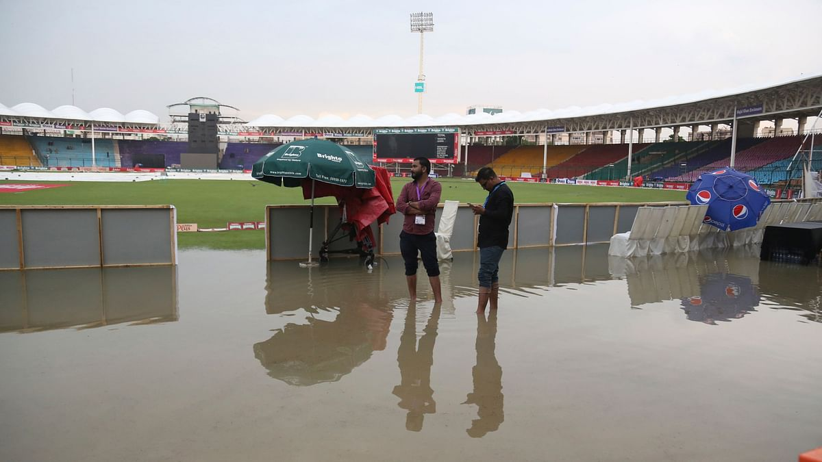 Officials stand at the National Stadium after rain in Karachi, Pakistan, Friday, Sept. 27, 219. Heavy rain has delayed the start of the first one-day international between Pakistan and Sri Lanka.